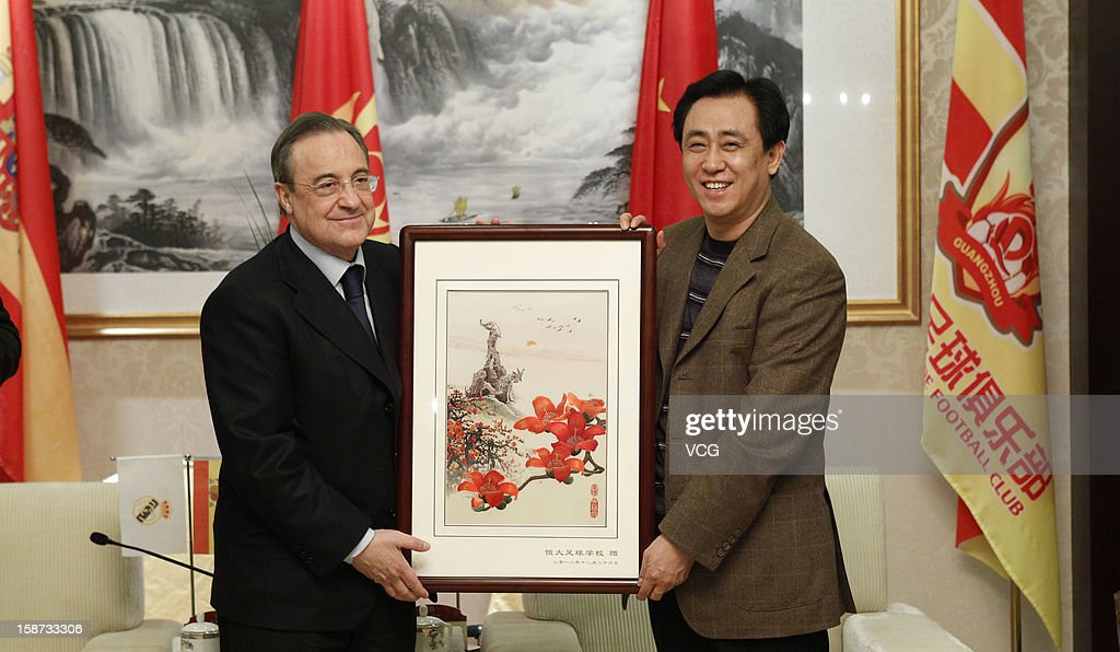 Guangzhou Evergrande owner Xu Jiayin (R) delivers a gift to Real Madrid president <a gi-track='captionPersonalityLinkClicked' href=/galleries/search?phrase=Florentino+Perez&family=editorial&specificpeople=567584 ng-click='$event.stopPropagation()'>Florentino Perez</a> at Hengda Hotel on December 26, 2012 in Guangzhou, China. <a gi-track='captionPersonalityLinkClicked' href=/galleries/search?phrase=Florentino+Perez&family=editorial&specificpeople=567584 ng-click='$event.stopPropagation()'>Florentino Perez</a> and his delegation are on a multi-day visit to Guangzhou Evergrande FC, who has a cooperation agreement with Real Madrid that has led to the creation of a football school in Qingyuan.