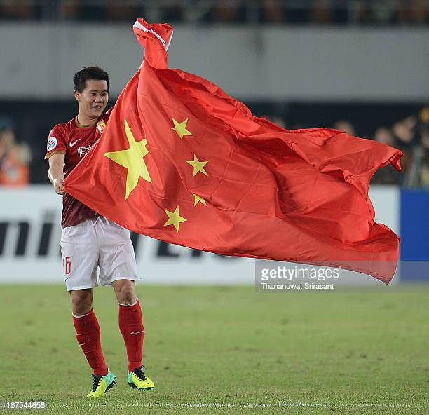 Guangzhou Evergrande player Huang Bowen celebrates with Chinese flag after winning the 2013 AFC Champions League final at Guangzhou Tianhe Sport...