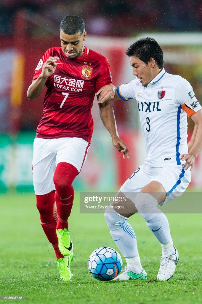 guangzhou forward alan douglas de carvalho fights for the ball with kashima defender shoji gen during