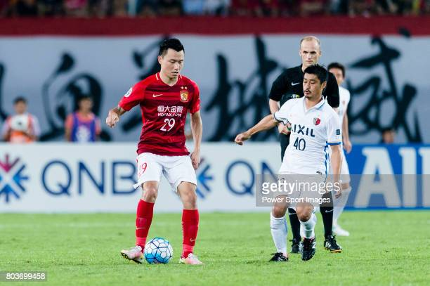 Guangzhou Forward Gao Lin fights for the ball with Kashima Midfielder Ogasawara Mitsuo during the AFC Champions League 2017 Round of 16 match between...