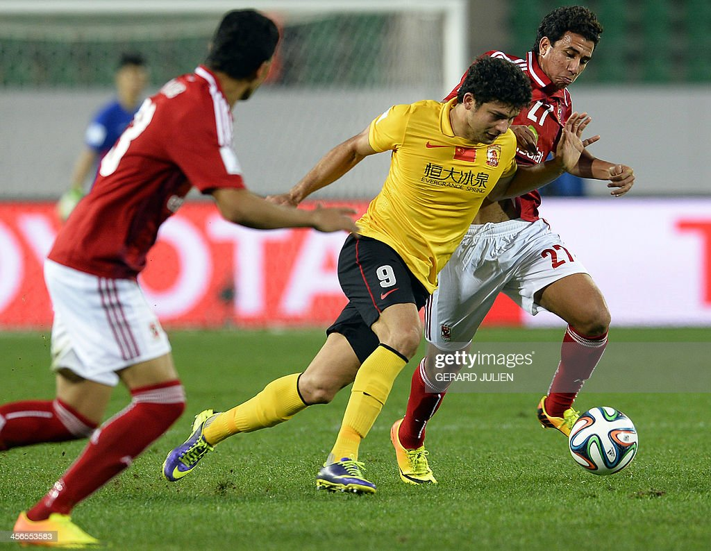 Guangzhou s Chinese mildfielder Dario Conca C is defended by Al