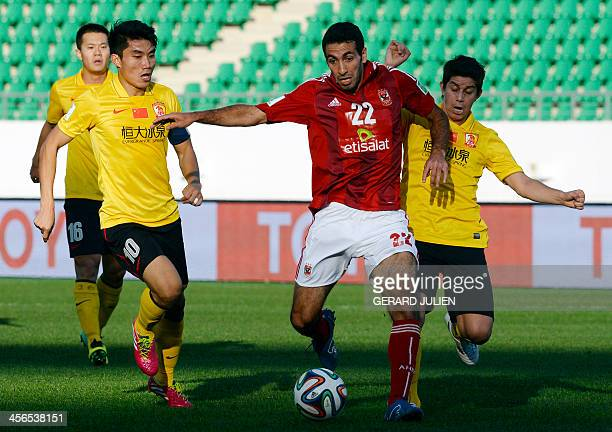 Guangzhou's Chinese mildfielder Zheng Zhi and Argenitinian midfielder Dario Conca defend against Al Ahly's Egyptian mildfielder Mohamed Aboutrika...