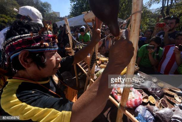 A Guarani shaman performs a ritual during the Native Seeds Fair at a square in downtown Asuncion on July 28 2017 Farmers at the fair exchange their...