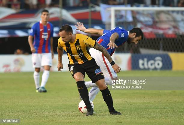 Guarani's Marcelo Canete vies for the ball with Cerro Porteno's Juan Aguilar during the Paraguayan Clausura tournament final football match on...