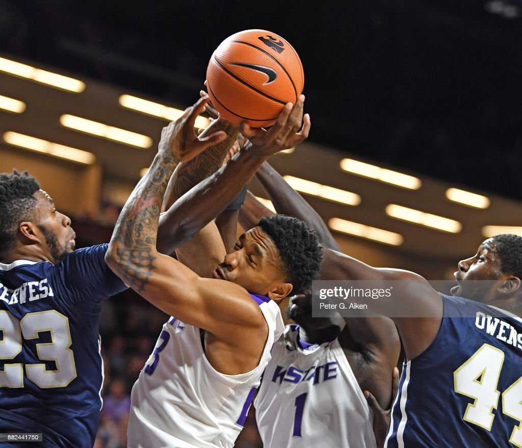 Guard Amaad Wainright #23 of the Kansas State Wildcats goes for a rebound between defenders Emmanuel Nzekwesi #23 and Albert Owens #44 of the Oral Roberts Golden Eagles during the first half on November 29, 2017 at Bramlage Coliseum in Manhattan, Kansas.