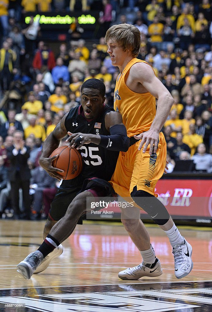 Guard Anthony Beane #25 of the Southern Illinois Salukis drives against guard Ron Baker #31 of the Wichita State Shockers during the first half on February 11, 2014 at Charles Koch Arena in Wichita, Kansas.