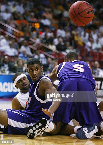Guard Arinze Onuaku of the Syracuse Orange battle for a loose ball with guard Walt Harris and forward Zach Williams of the Stephen F Austin...