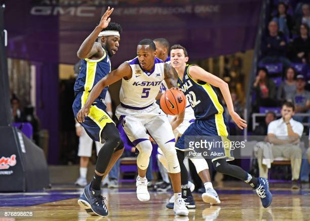 Guard Barry Brown of the Kansas State Wildcats drives with the ball against pressure form defender Ruben Fuamba of the Northern Arizona Lumberjacks...