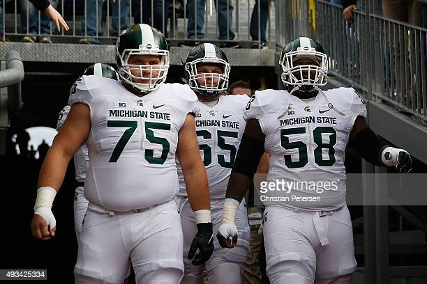 Guard Benny McGowan and center Devyn Salmon of the Michigan State Spartans take the field before the college football game against the Michigan...