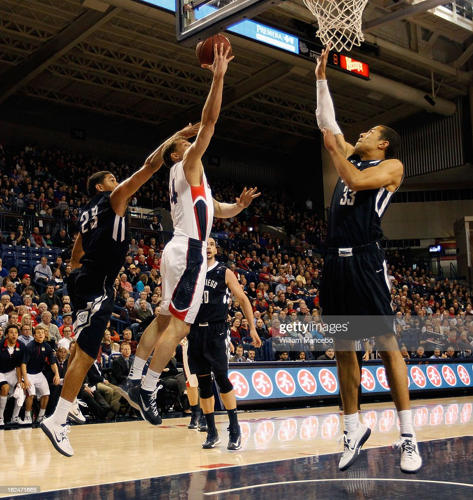 Guard Brian Bhaskar#14 of the Gonzaga Bulldogs goes to the hoop while forward Trey Guidry #23 and center Jito Kok #33 of the San Diego Toreros defend during the second half of the game at McCarthey Athletic Center on February 23, 2013 in Spokane, Washington.