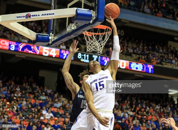 Guard Chandler Hutchison of the Boise State Broncos shoots from under the hoop against the defense of forward Norbert Janicek of the Utah State...