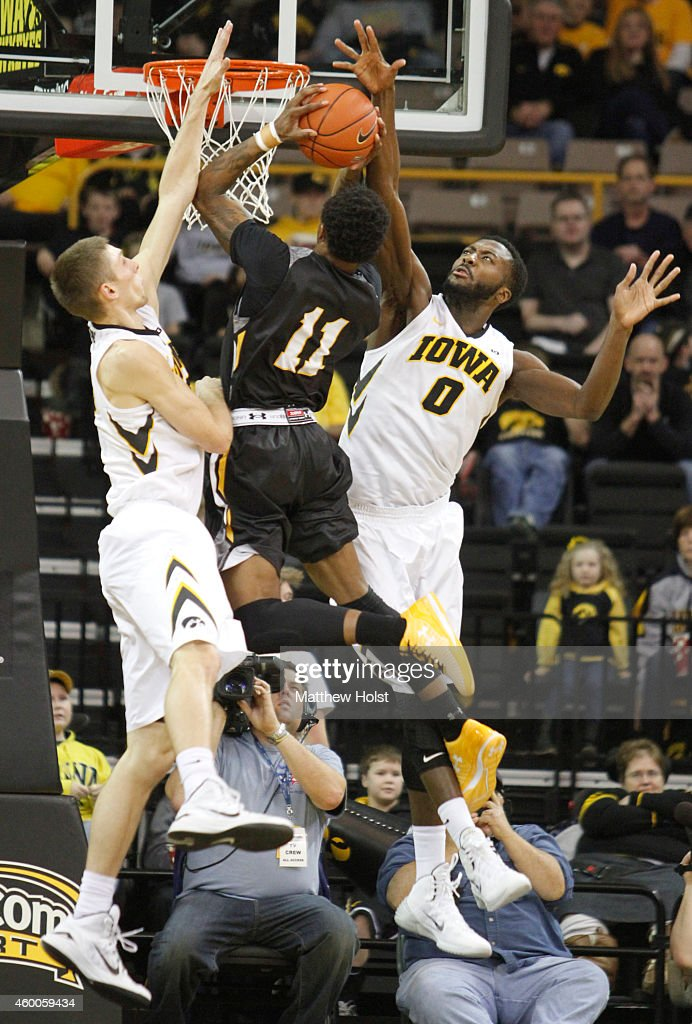 Guard <a gi-track='captionPersonalityLinkClicked' href=/galleries/search?phrase=Charles+Taylor&family=editorial&specificpeople=240314 ng-click='$event.stopPropagation()'>Charles Taylor</a> #11 of the UMBC Retrievers drives tot eh basket between center Gabriel Olaseni #0 and forward Jarrod Uthoff #20 of the Iowa Hawkeyes, in the first half on December 6, 2014 at Carver-Hawkeye Arena, in Iowa City, Iowa.