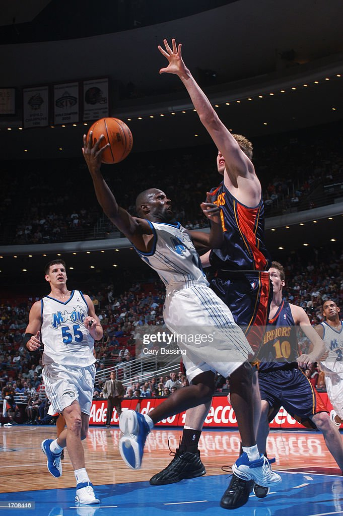 Guard Darrell Armstrong #10 of the Orlando Magic shoots against forward Troy Murphy #1 of the Golden State Warriors during the game at TD Waterhouse Centre on December 13, 2002 in Orlando, Florida. The Magic won 111-85.