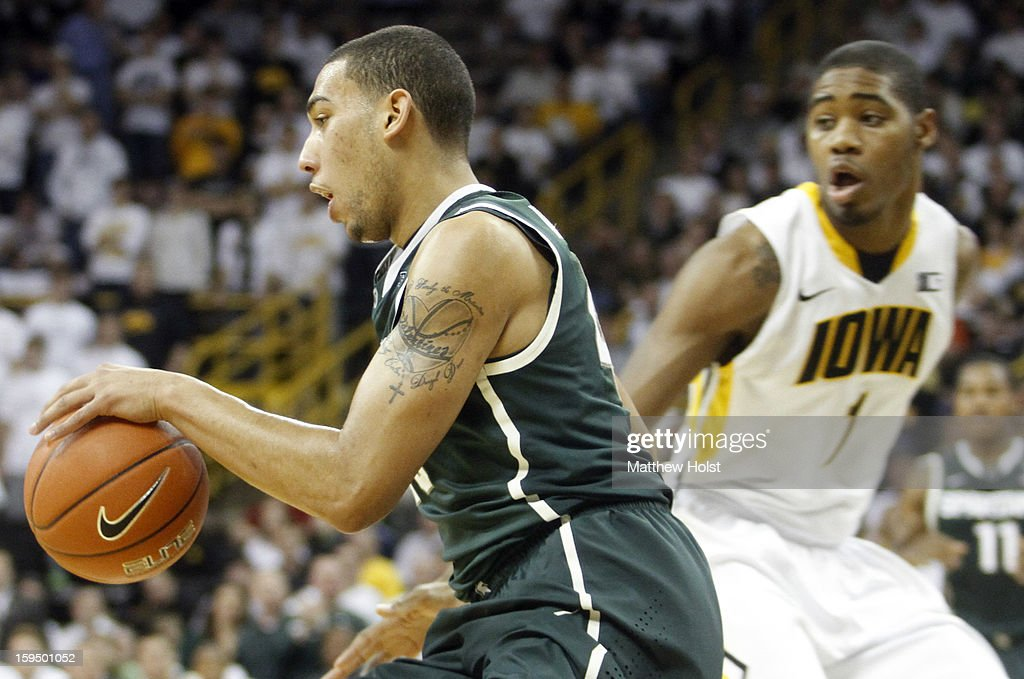 Guard Denzel Valentine #45 of the Michigan State Spartans brings the ball down the court during the first half past forward Melsahn Basabe #1 of the Iowa Hawkeyes on January 10, 2013 at Carver-Hawkeye Arena in Iowa City, Iowa. Michigan State won 62-59.