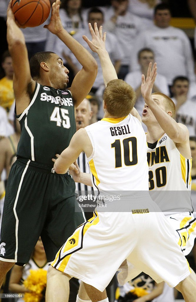 Guard Denzel Valentine #45 of the Michigan State Spartans looks to pass the ball during the first half against guard Mike Gesell #10 and forward Aaron White #30 of the Iowa Hawkeyes on January 10, 2013 at Carver-Hawkeye Arena in Iowa City, Iowa. Michigan State won 62-59.