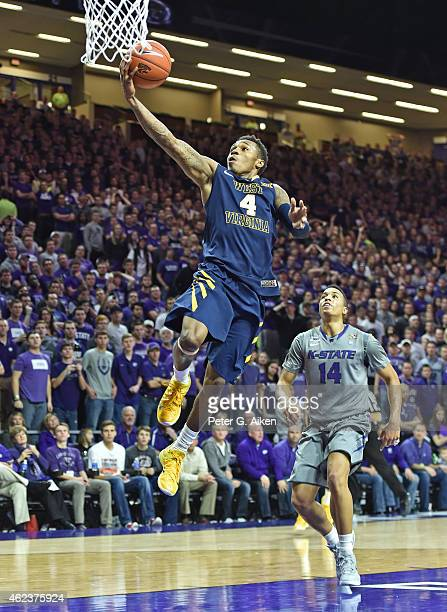 Guard Dexter Miles Jr #4 of the West Virginia Mountaineers scores off a fast brake past guard Justin Edwards of the Kansas State Wildcats during the...