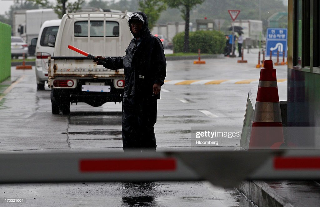 A guard directs vehicles passing through a gate at the Customs, Immigration and Quarantine (CIQ) office as they travel toward the Gaeseong Industrial Complex, on a road linked to North Korea, near the demilitarized zone (DMZ) in Paju, South Korea, on Friday, July 12, 2013. North Korea notified South Korea today that it has deferred two separate sets of talks on the tours and the family reunions it proposed yesterday, and said it wants to focus on the ongoing dialog to reopen the joint Gaeseong industrial zone, the Souths Unification Ministry said in an e-mailed statement. The two sides yesterday decided to hold talks in Gaeseong on July 15, which will be their third round in one week, on normalizing operations in Gaeseong after the North unilaterally recalled its workers in April. Photographer: SeongJoon Cho/Bloomberg via Getty Images