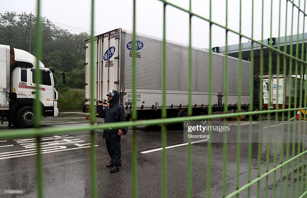 A guard directs vehicles returning from Gaeseong Industrial Complex at the Customs, Immigration and Quarantine (CIQ) office near the demilitarized zone (DMZ) in Paju, South Korea, on Friday, July 12, 2013. North Korea notified South Korea today that it has deferred two separate sets of talks on the tours and the family reunions it proposed yesterday, and said it wants to focus on the ongoing dialog to reopen the joint Gaeseong industrial zone, the Souths Unification Ministry said in an e-mailed statement. The two sides yesterday decided to hold talks in Gaeseong on July 15, which will be their third round in one week, on normalizing operations in Gaeseong after the North unilaterally recalled its workers in April. Photographer: SeongJoon Cho/Bloomberg via Getty Images