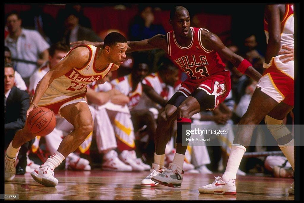 Guard Doc Rivers of the Atlanta Hawks tries to fend off guard Michael Jordan of the Chicago Bulls during a game at the Omni in Atlanta Georgia