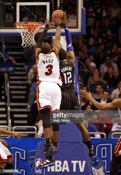 Guard Dwyane Wade of the Miami Heat blocks the shot of center Dwight Howard of the Orlando Magic at Amway Arena on February 3 2011 in Orlando Florida...