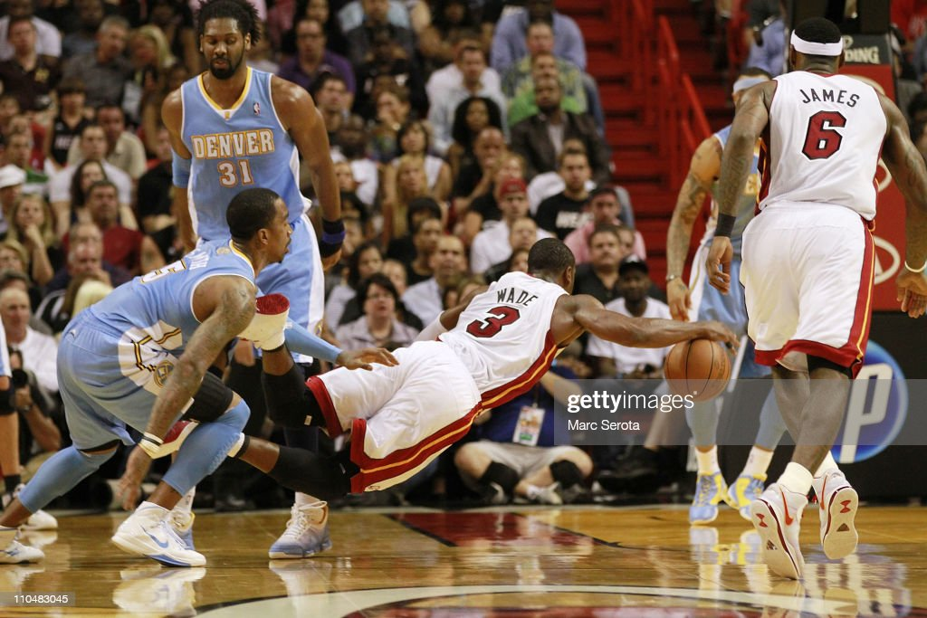 Guard <a gi-track='captionPersonalityLinkClicked' href=/galleries/search?phrase=Dwyane+Wade&family=editorial&specificpeople=201481 ng-click='$event.stopPropagation()'>Dwyane Wade</a> #3 of the Miami Heat is fouled by guard <a gi-track='captionPersonalityLinkClicked' href=/galleries/search?phrase=J.R.+Smith&family=editorial&specificpeople=201766 ng-click='$event.stopPropagation()'>J.R. Smith</a> (R) of the Denver Nuggets at American Airlines Arena on March 19, 2011 in Miami, Florida. The Heat defeated the Nuggets 103-98.
