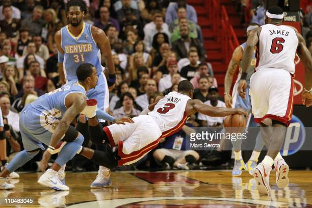 Guard Dwyane Wade of the Miami Heat is fouled by guard JR Smith of the Denver Nuggets at American Airlines Arena on March 19 2011 in Miami Florida...