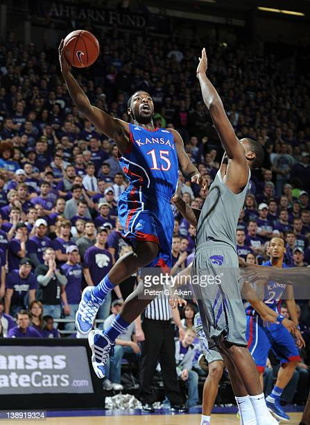Guard Elijah Johnson of the Kansas Jayhawks drives to the basket against forward Jordan Henriquez of the Kansas State Wildcats during the first half...
