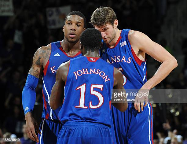 Guard Elijah Johnson of the Kansas Jayhawks talks with teammates Jeff Withey and Thomas Robinson during the second half against the Kansas State...