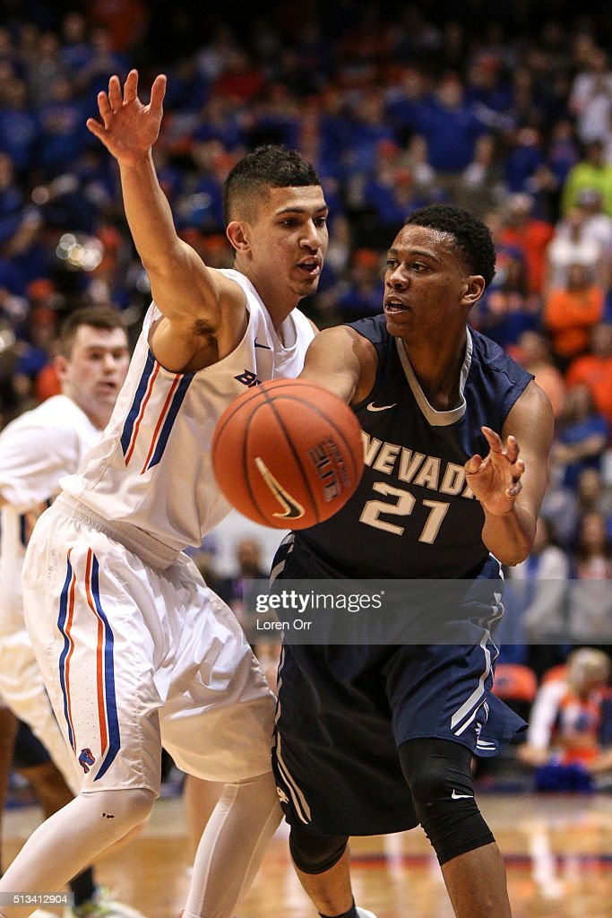 Guard Eric Cooper Jr #21 of the Nevada Wolf Pack passes under pressure from guard Lonnie Jackson of the Boise State Broncos during first half action...