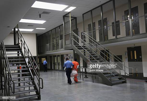 A guard escorts an immigrant detainee from his 'segregation cell' back into the general population at the Adelanto Detention Facility on November 15...