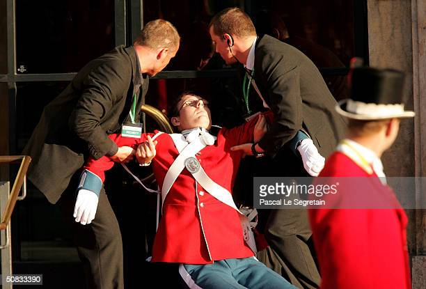 A guard faints as he waits for the arrival of Miss Mary Elizabeth Donaldson and Danish Crown Prince Frederik for a Gala Performance in their honor at...