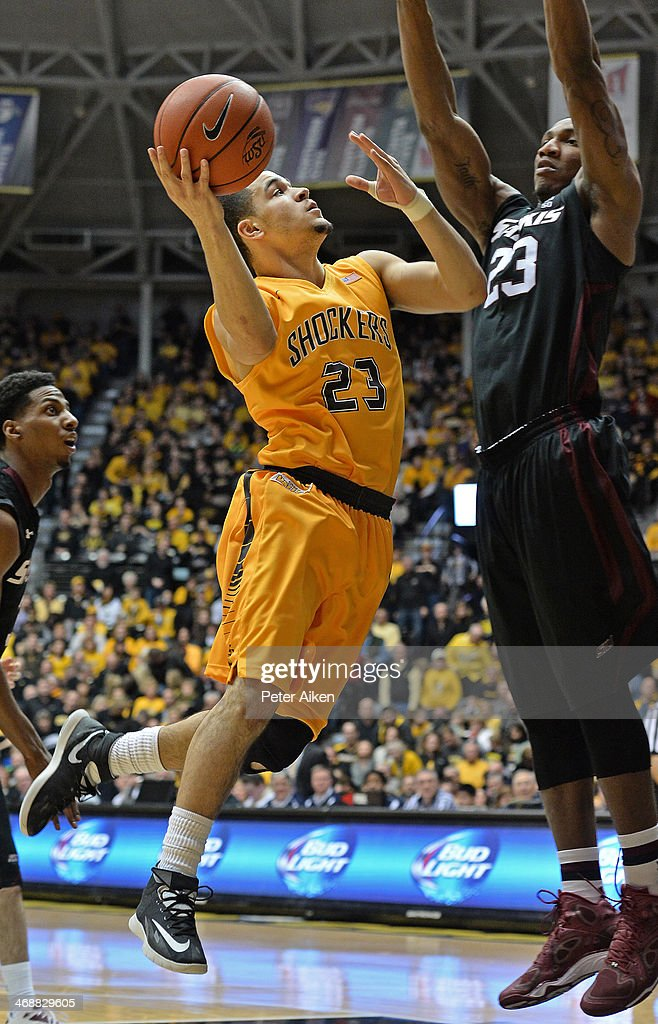 Guard Fred VanVleet (L) of the Wichita State Shockers drives to the basket against forward Bola Olaniyan (R) of the Southern Illinois Salukis during the second half on February 11, 2014 at Charles Koch Arena in Wichita, Kansas. Wichita State won 78-67.