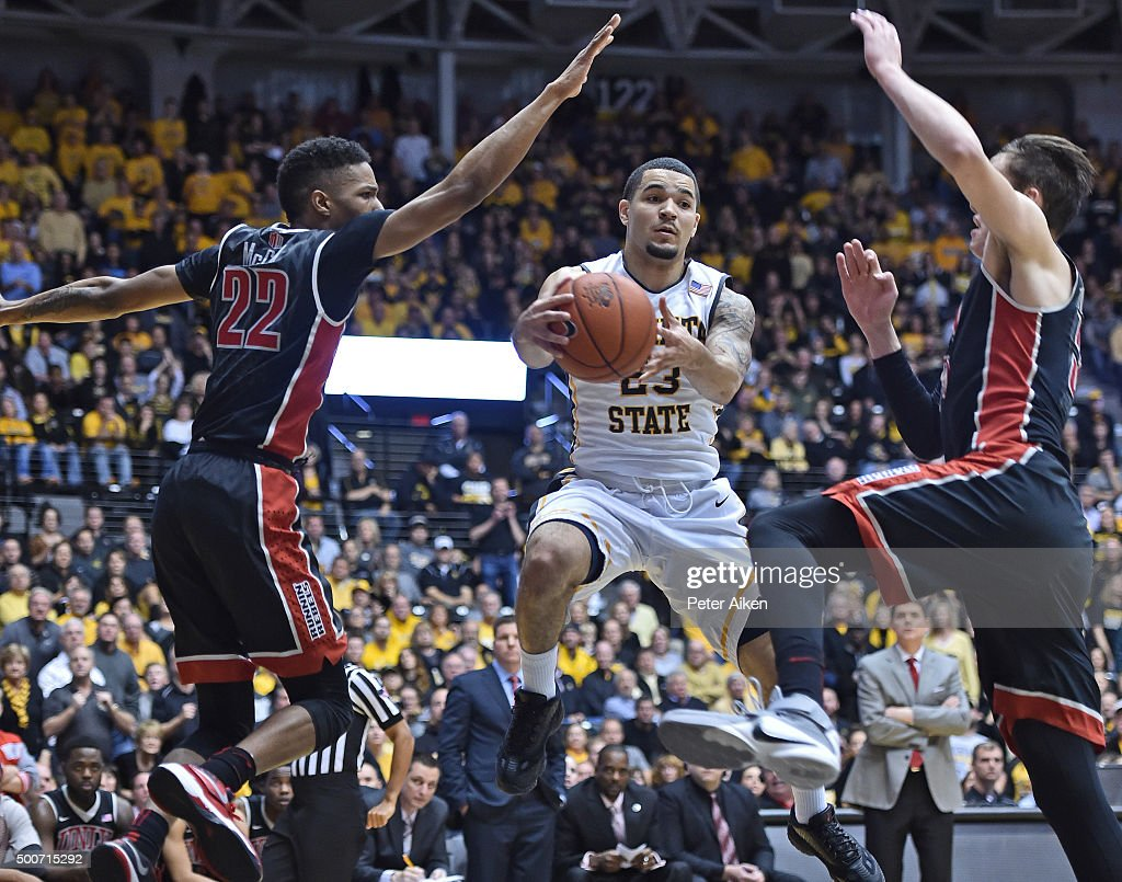Guard Fred VanVleet #23 of the Wichita State Shockers drives with the ball against defenders Stephen Zimmerman Jr. #33 and Patrick McCaw #22 of the UNLV Rebels during the first half on December 9, 2015 at Charles Koch Arena in Wichita, Kansas.