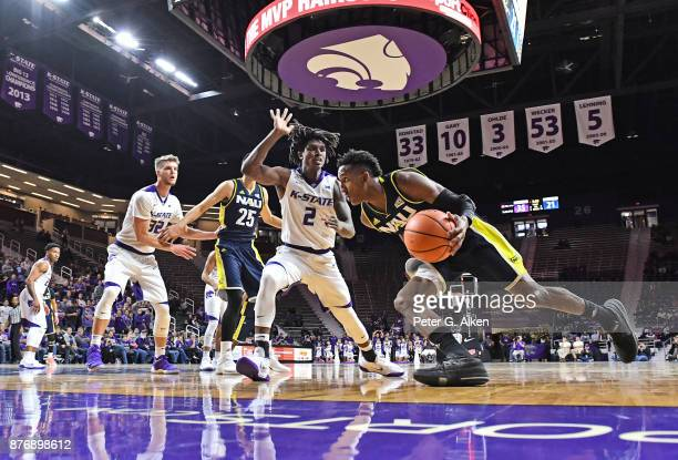 Guard Gino Littles of the Northern Arizona Lumberjacks drives baseline against guard Cartier Diarra#2 of the Kansas State Wildcats during the first...