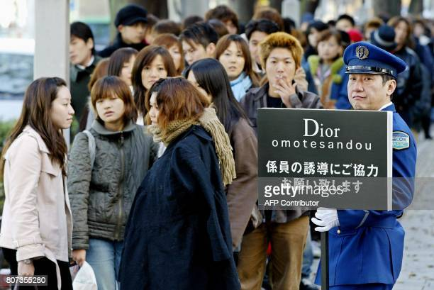 A guard holds a banner to control people waiting in line for the opening of the Christian Dior flagship boutique in Tokyo's fashion district Harajuku...