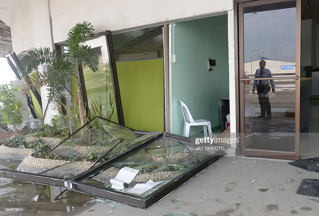 A guard is reflected in a glass door next to a a damage government office following a 7.1-magnitude quake in Cebu on October 15, 2013. A powerful earthquake killed at least 73 people on October 15 as it tore down modern buildings, destroyed historic churches and triggered terrified stampedes across popular tourist islands in the Philippines. AFP PHOTO / Jay DIRECTO