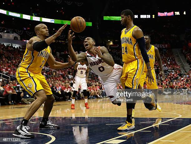 Guard Jeff Teague of the Atlanta Hawks is fouled by forward Paul Geroge of the Indiana Pacers while Pacers forward David West looks on in Game 6 of...