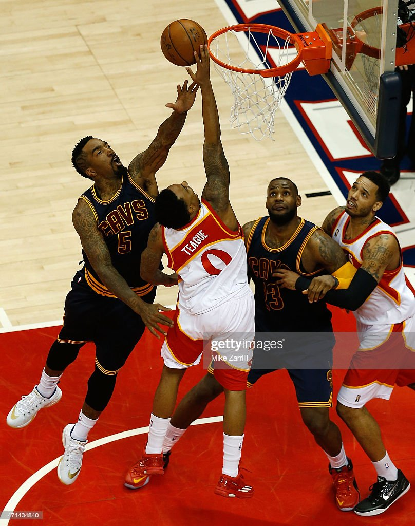 Guard Jeff Teague of the Atlanta Hawks shoots over guard JR Smith and forward LeBron James of the Cleveland Cavaliers while forward Mike Scott of the...