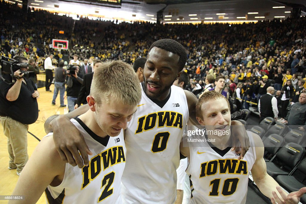 Guard Josh Oglesby center Gabriel Olaseni and guard Mike Gesell of the Iowa Hawkeyes walk off the floor after defeating the Northwestern Wildcats on...