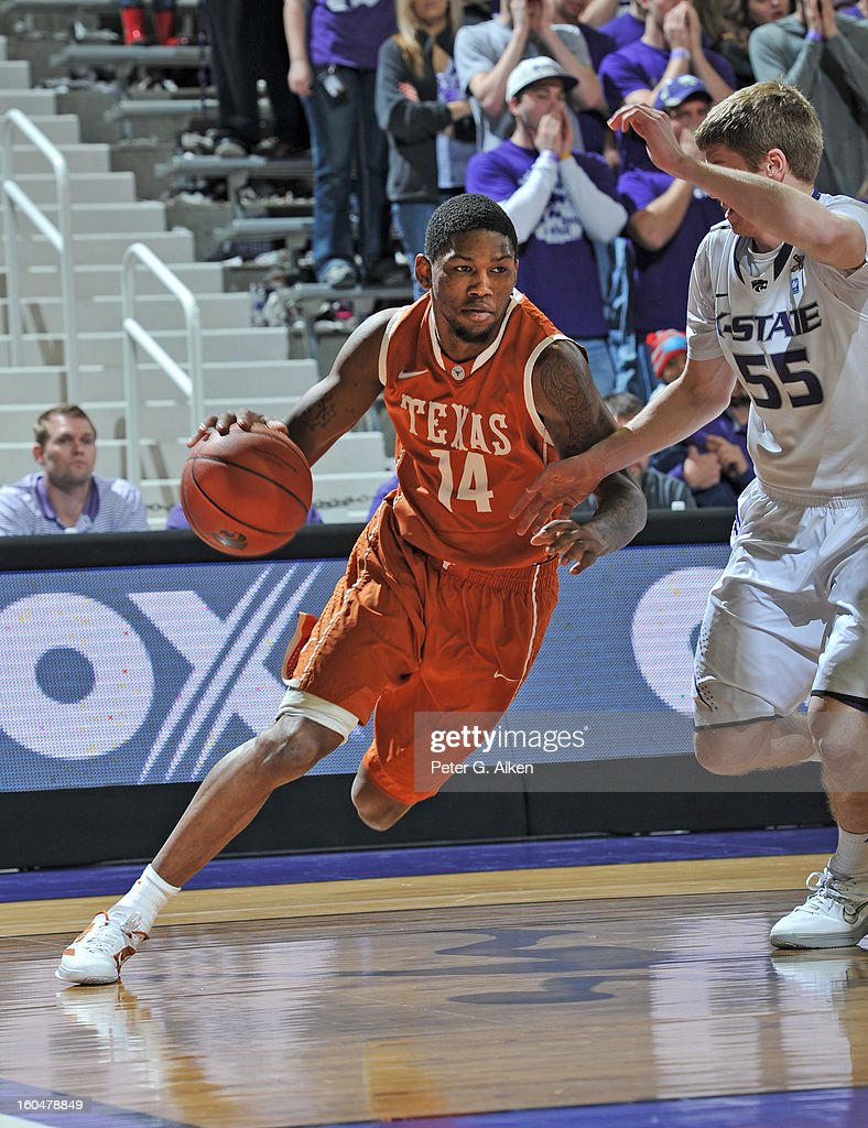 Guard Julien Lewis #14 of the Texas Longhorns drives to the basket against Will Spradling #55 of the Kansas State Wildcats during the first half on January 30, 2013 at Bramlage Coliseum in Manhattan, Kansas.