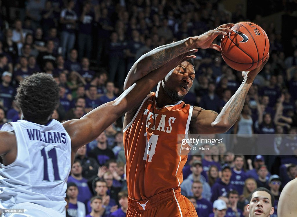 Guard Julien Lewis #14 of the Texas Longhorns grabs a rebound against guard Nino Williams #11 of the Kansas State Wildcats during the second half on January 30, 2013 at Bramlage Coliseum in Manhattan, Kansas. Kansas State defeated Texas 83-57.