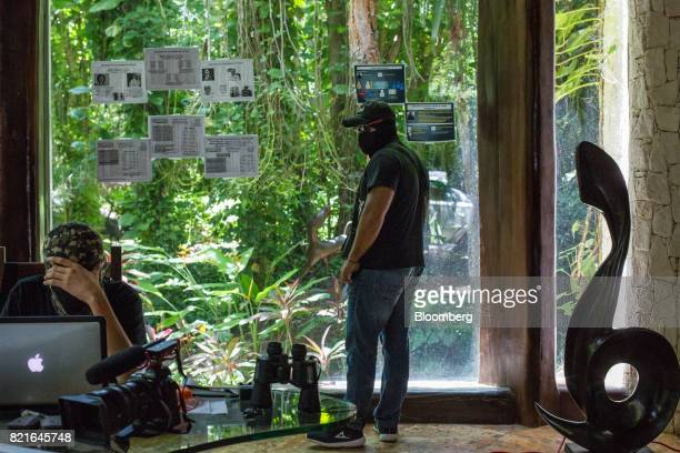 A guard keeps watch as a hacker uses surveillance equipment to check on local government officials who may be colluding with the country's drug...