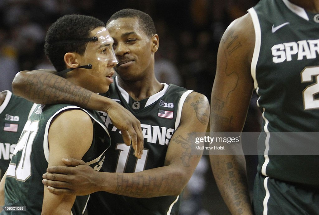 Guard Keith Appling #11 of the Michigan State Spartans hugs guard Travis Trice #20 after their match-up against the Iowa Hawkeyes on January 10, 2013 at Carver-Hawkeye Arena in Iowa City, Iowa. Michigan State won 62-59.