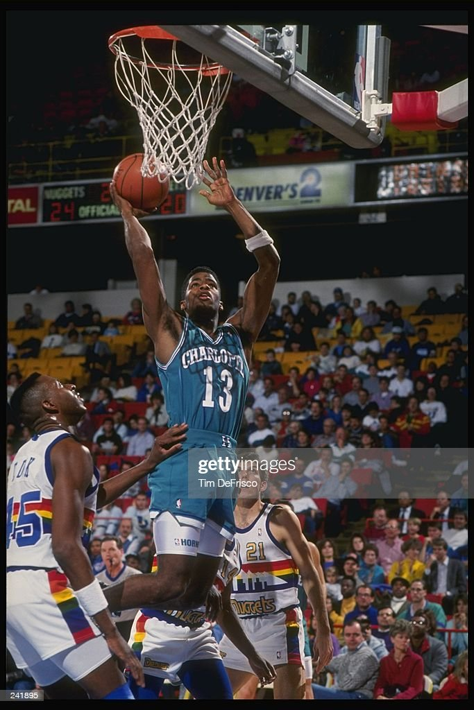 Guard Kendall Gill of the Charlotte Hornets goes up for two as forward Anthony Cook of the Denver Nuggets waits for the rebound during a game at the...