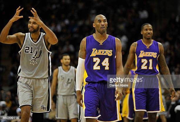 Guard Kobe Bryant and forward Ed Davis of the Los Angeles Lakers walk up court as forward Tim Duncan left of the San Antonio Spurs reacts to a call...