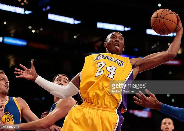 Guard Kobe Bryant of the Los Angeles Lakers drives the lane into defenders Klay Thompson and David Lee of the Golden State Warriors during first...