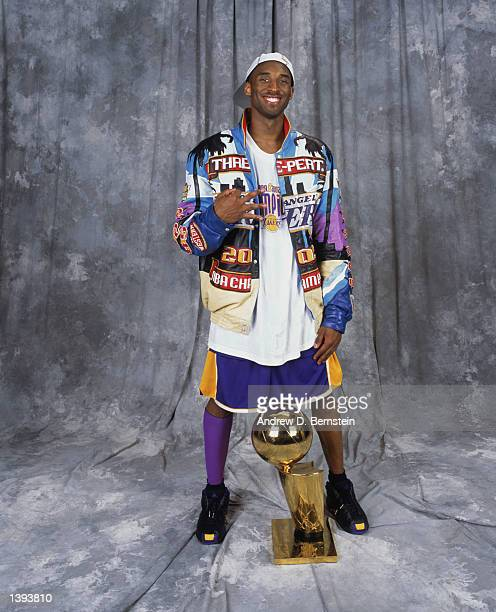 Guard Kobe Bryant of the Los Angeles Lakers gestures in reference to the 'threepeat' as he stands with the trophy after winning Game Four of the 2002...