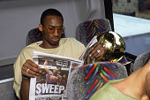 Guard Kobe Bryant of the Los Angeles Lakers reads the headlines as he sits in the team bus with the championship trophy after winning Game Four of...