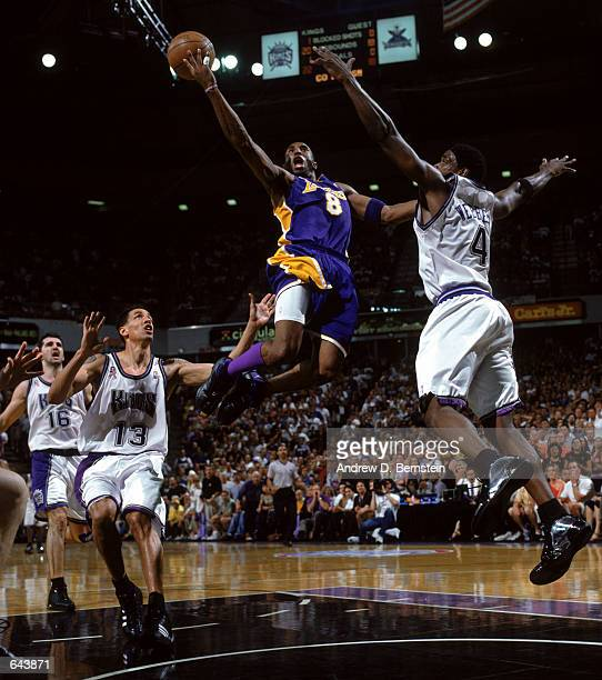 Guard Kobe Bryant of the Los Angeles Lakers soars for the layup over Chris Webber and Doug Christie of the Sacramento Kings in game 7 of the 2002 NBA...