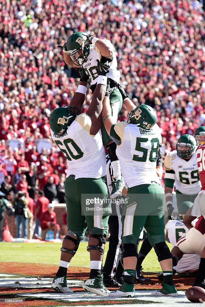 Guard LaQuan McGowan offensive tackle Spencer Drango and running back Devin Chafin of the Baylor Bears celebrate a touchdown against the Oklahoma...